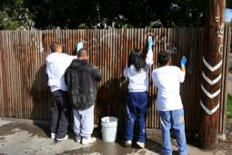 Kids cleaning the graphite on the Fence