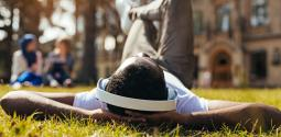 Young man laying in grass with headphones on