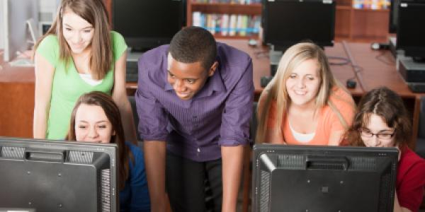 Students gathered around two computers