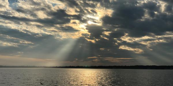 image of water and sun shining through clouds
